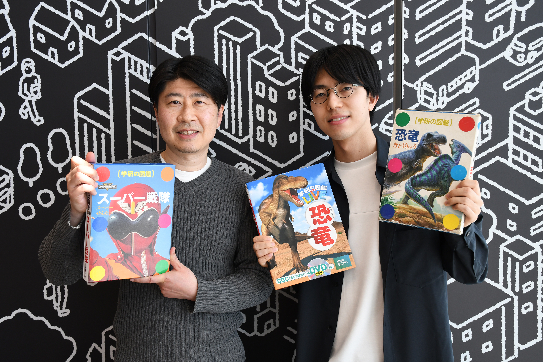 松原(右)が持つのが1990年発行の『学研の図鑑 恐竜』、2014年発行の『学研の図鑑LIVE 恐竜』、そして芳賀(左)が持つのが今年2021年発売となった『学研の図鑑 スーパー戦隊』